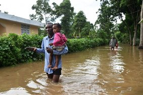 a father and daughter walking through flood waters in Haiti