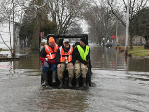 disaster response volunteers riding tractor to avoid flood waters