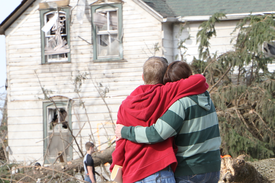 A forlorn family looking at their destroyed house following a disaster